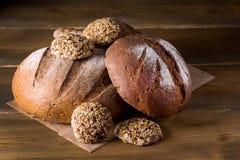 Variedade de Loafs Rye cozido fresco e de pão inteiro da grão na variedade escura da foto do fundo de madeira da textura de espaç Foto de Stock Royalty Free