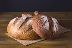 Variedade de Loafs Rye cozido fresco e de pão inteiro da grão na variedade escura da foto do fundo de madeira da textura de pão t Fotos de Stock Royalty Free