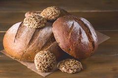 Variedade de Loafs Rye cozido fresco e de pão inteiro da grão na variedade escura da foto do fundo de madeira da textura de pão t Fotos de Stock