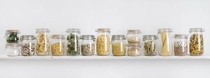 Variedade de mantimentos crus nos frascos de vidro arranjados na prateleira imagem de stock