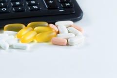 Variedade de medicamentação na frente da calculadora no branco Fotos de Stock