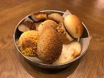 Variedade de pães pequenos na cesta do metal na superfície de madeira fotografia de stock royalty free