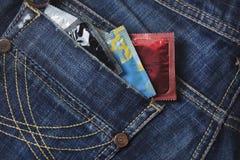 Variedade de preservativos no bolso de calças de ganga Fotografia de Stock Royalty Free