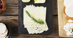Variedade de queijo, de azeitonas, de biscoitos e de ervas dos alecrins na tabela de madeira vídeos de arquivo
