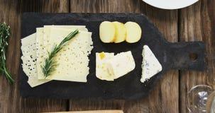 Variedade de queijo, de azeitonas, de biscoitos e de ervas dos alecrins na tabela de madeira filme