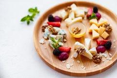 Variedade de queijos diferentes na bandeja de madeira imagens de stock royalty free
