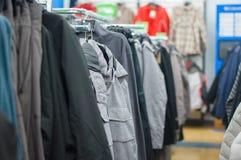 Variedade de revestimentos, de vestes e de camisolas em carrinhos fotos de stock