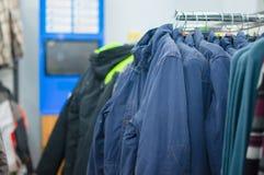 Variedade de revestimentos, de vestes e de camisolas em carrinhos fotografia de stock