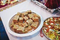 Variedade de sobremesa doce indiana do prato feita do feijão na tabela de madeira do weave imagem de stock