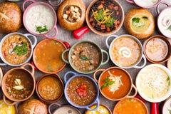 Variedade de sopas decoradas em umas bacias coloridas Imagens de Stock Royalty Free
