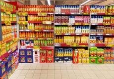 Variedade de suco de fruto nas prateleiras em um supermercado Imagens de Stock