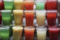 Variedade de sucos de fruto no vidro plástico imagem de stock royalty free