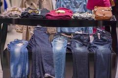 Variedade de t-shirt e de calças de brim da cor na tabela foto de stock