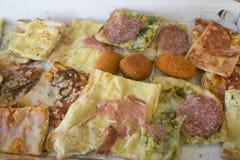 A variedade de tipos de pizza cortou nas partes e no arancine Imagem de Stock Royalty Free