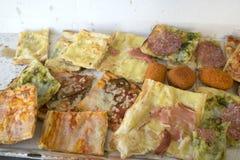 A variedade de tipos de pizza cortou nas partes e no arancine Fotografia de Stock