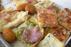 A variedade de tipos de pizza cortou nas partes e no arancine Foto de Stock