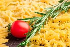 Variedade de tipos e formulários do macarrão seco com tomates e alecrins Alimento cru ou textura do macarrão italiano: massa imagem de stock royalty free