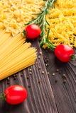 Variedade de tipos e formulários do macarrão seco com tomates e alecrins Alimento cru ou textura do macarrão italiano: massa imagens de stock