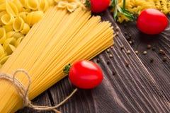 Variedade de tipos e formulários do macarrão seco com tomates e alecrins Alimento cru ou textura do macarrão italiano: massa foto de stock royalty free