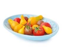 Variedade de tomates de cereja da herança na bacia azul isolada imagens de stock royalty free