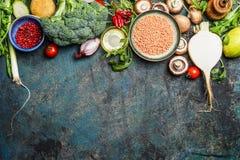 Variedade de vegetais, de lentilha vermelha e de ingredientes para o cozimento saudável no fundo rústico, vista superior, beira h Fotos de Stock