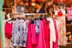 Variedade de vestidos e de camisas no carrinho na alameda foto de stock