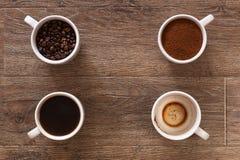 Variedade de xícaras de café e de feijões de café na tabela de madeira velha Quatro xícaras de café, fases de bebida - feijão, te Fotos de Stock Royalty Free