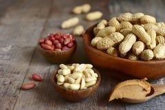 Variedade do amendoim no bacias e manteiga de amendoim de madeira fotografia de stock