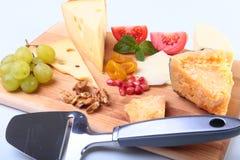 Variedade do queijo com frutos, uvas, porcas e faca do queijo em uma bandeja de madeira do serviço Fotografia de Stock Royalty Free