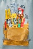 Variedade do trabalho feito com ferramentas da construção na correia da ferramenta na parte traseira do concreto imagens de stock royalty free