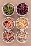 Variedade dos feijões e das lentilhas no isolado de madeira da colher no branco Imagem de Stock Royalty Free