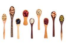 Variedade dos feijões e das lentilhas no isolado de madeira da colher no branco Fotos de Stock Royalty Free