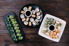 Variedade dos rolos de sushi na tabela de madeira, configuração lisa fotos de stock royalty free