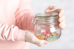 Variedade fêmea da posse de doces jely coloridos no frasco Imagem de Stock Royalty Free
