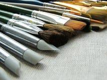Variedade grande de escovas, de ferramentas para pintar e de escultura no fundo de linho da tela imagens de stock