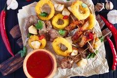 Variedade grelhada das carnes, anéis de cebola nas côdeas de pão ralado, deco dos biscoitos Imagem de Stock Royalty Free