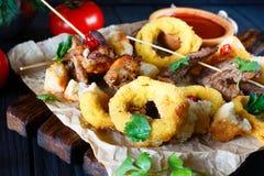 Variedade grelhada das carnes, anéis de cebola nas côdeas de pão ralado, deco dos biscoitos Imagens de Stock