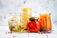 Variedade posta de conserva das salmouras que preserva frascos Couve-flor caseiro, polpa, cenouras, salmouras das pimentas de pim Foto de Stock Royalty Free