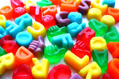 Variedade superior do dedo de letras coloridas dos doces no fundo branco Foto de Stock