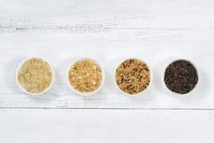 Variedades de arroz en cuencos encima de la madera blanca Imagen de archivo