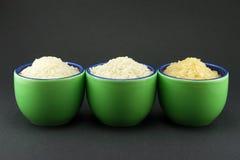 Variedades de arroz en tres pequeñas tazas verdes Fotografía de archivo libre de regalías