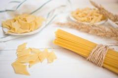 variedades de pastas en una tabla de madera blanca, espagueti, Penne, maltagliati, cocina local fotos de archivo