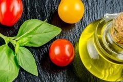 Variedades de tomates y de aceite de oliva coloridos Fotografía de archivo