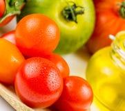 Variedades de tomates y de aceite de oliva coloridos Imagen de archivo libre de regalías