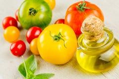 Variedades de tomates y de aceite de oliva coloridos Imagen de archivo