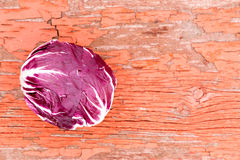 Variegated radicchio on grungy rustic wood. Variegated whole fresh purple and white radicchio, or Italian chicory, on grungy rustic wood with cracked red paint Stock Photos