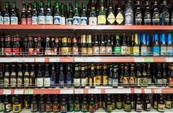 Varietà di birre elaborate belghe sull'esposizione dello scaffale del negozio fotografie stock