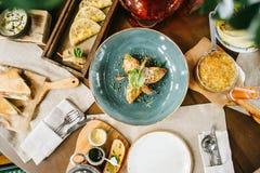 Varietà di cucina variopinta servita sui taglieri e sui piatti di legno fotografie stock