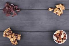 Varietà di dadi, di barre di granola e di cioccolato su fondo di legno fotografie stock libere da diritti