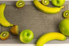 Varietà di frutti verdi con tessuto grigio vuoto La vista dalla parte superiore Fotografia Stock